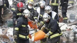 Firefighters carry a body on a stretcher from the rubble of the collapsed building in Rosny-Sous-Bois