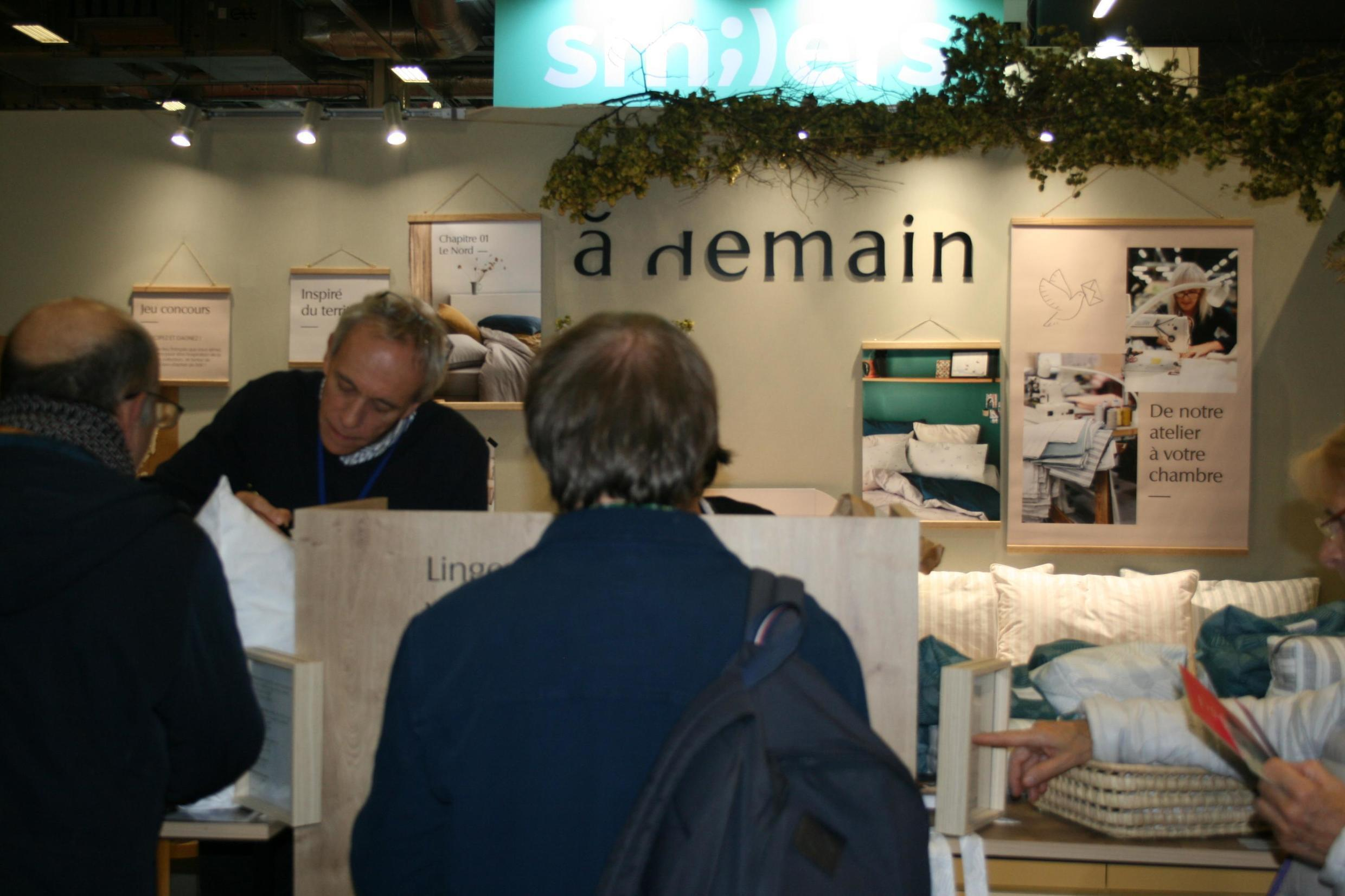 """Bed-maker Bernard Vanderschooten takes an order for new bed linen and pillows made in his factory in northern France at the """"Made in France"""" fair in Paris, 10 November 2019"""