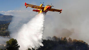 A Canadair firefighting aircraft drops water on a wildfire