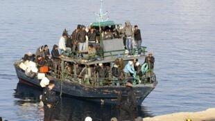 Barco com imigrantes da África do norte chegando em Lampedusa.