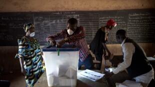 Un agent électoral portant un masque de protection enlève les sceaux d'une urne après le premier tour des législatives maliennes, à Bamako, le 29 mars 2020.