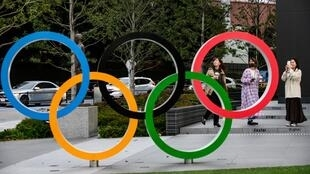 People take pictures of the Olympic Rings outside the closed Japan Olympic Museum in Tokyo on March 27, 2020, three days after the historic decision to postpone the 2020 Tokyo Olympic Games.