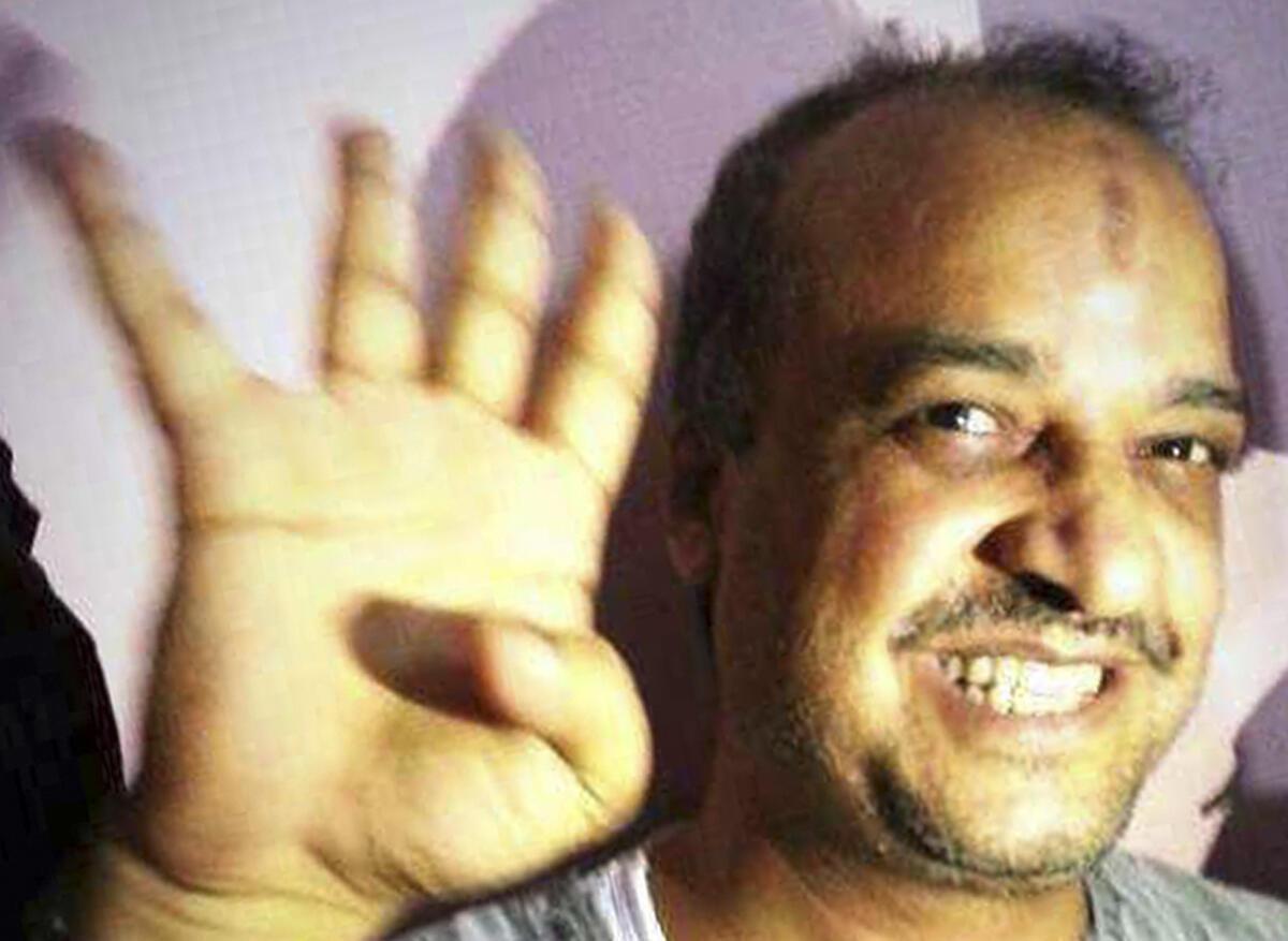 Mohamed el-Beltagi, lors de son arrestation le 29 août 2013 , faisant un signe en référence au camp pro-Morsi de la place Rabaa al-Adawiya, évacué le 14 août 2013.