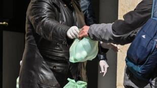 Un volontaire distribue de la nourriture à une personne en difficulté, à Rome en Italie (image d'illustration).