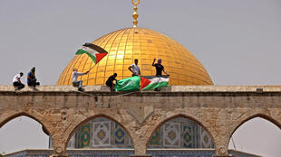 Palestinians wave the Palestinian and Hamas flags during fresh clashes with Israeli security forces in Jerusalem's Al-Aqsa mosque compound on May 21, 2021