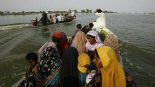 Villagers from flooded villages sit in a boat as they are rescued by volunteers in Patuja Lane near Shahdadkot