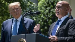 Le président américain Donald Trump écoute Moncef Slaoui, l'ancien chef de la division des vaccins de GlaxoSmithKlines, parler du développement d'un vaccin contre le coronavirus dans la roseraie de la Maison Blanche, le 15 mai 2020 à Washington.