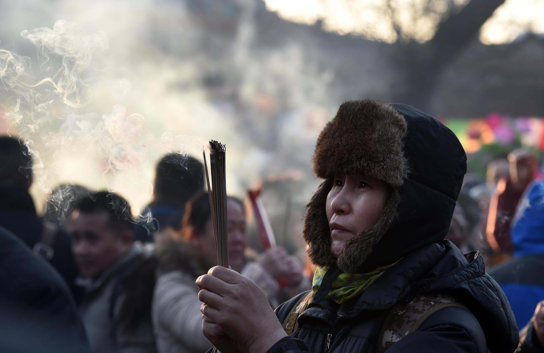 Para atrair sorte, uma chinesa queima incenso no templo de Yonghe, em Pequim.