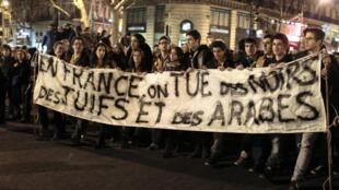 """""""Na França matam negros, judeus e árabes"""", diz a frase da faixa levada por participantes da marcha silenciosa em homenagem às vítimas do criminoso, na noite de segunda-feira, em Paris."""