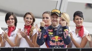 O alemão Sebastian Vettel comemora vitória no circuito de Monza neste domingo, 8 de setembro de 2013, cercado de promotoras da Fórmula 1.