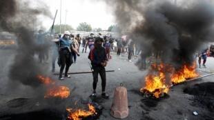 Des manifestants brûlent des pneus pour bloquer une rue à Bagdad, le 19 janvier 2020.