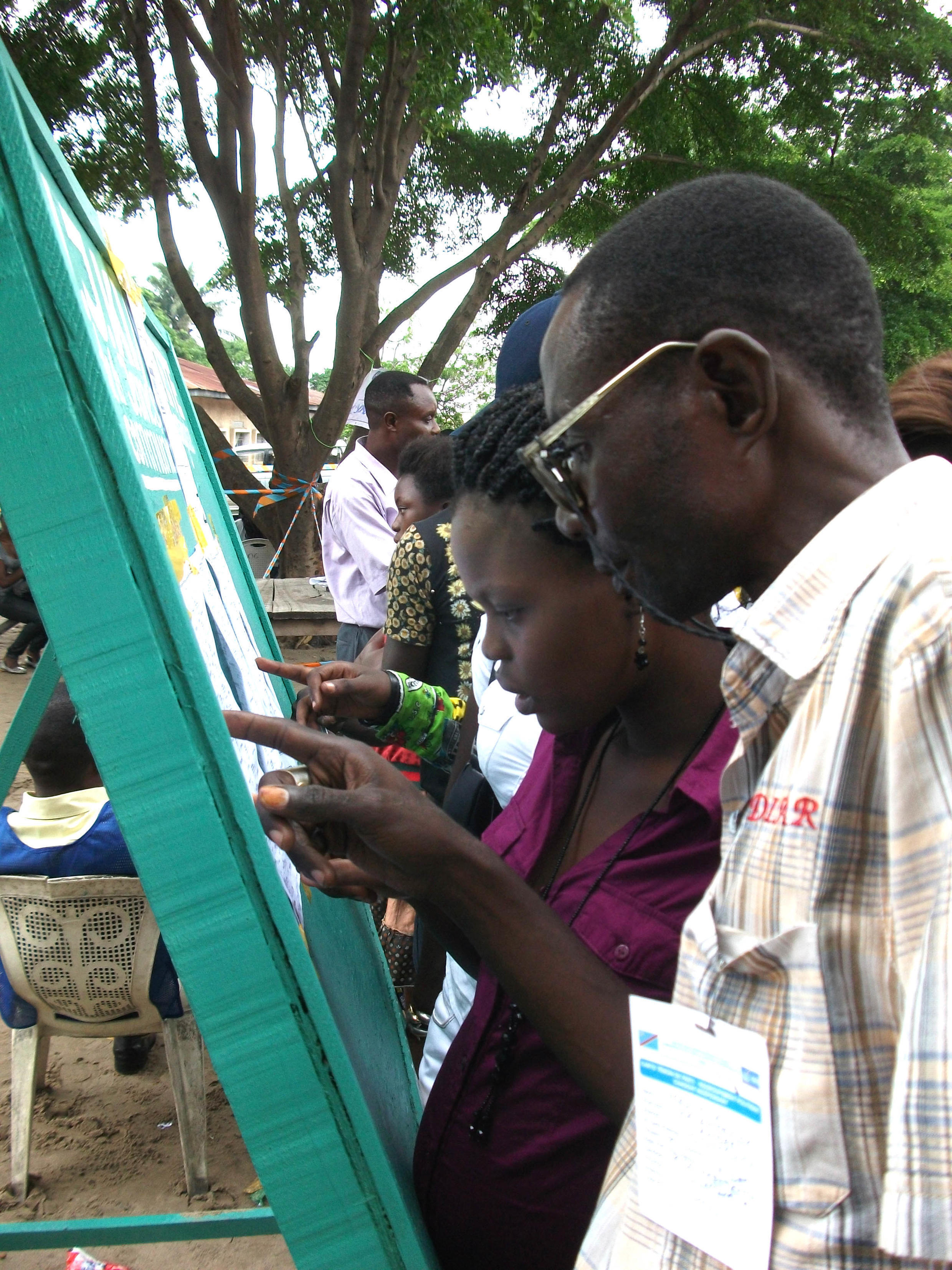 Voters searching for their names on the voter list in Matete, Kinshasa