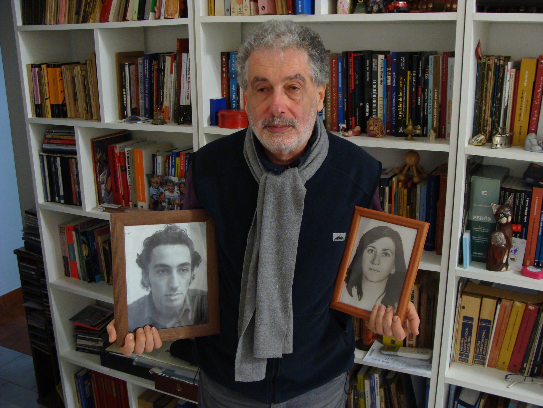 Edgardo Binstock segurando porta-retratos de Mónica Pinus de Binstock, esposa, e de Guillermo Binstock, irmão.
