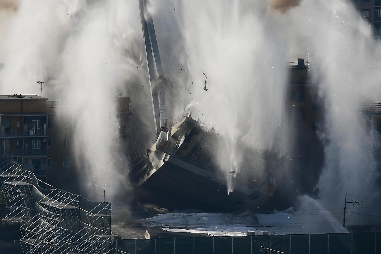 Le tablier du pont Morandi touche le sol dans un nuage de fumée, ce vendredi 28 juin.