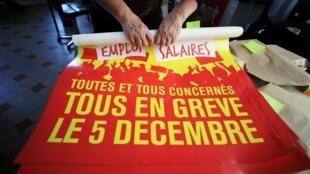 法國總工會(CGT)一名成員在巴黎交易所廣場展示12月5日罷工號召