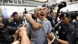 Polícia reprime manifestante em Kuala Lampur, neste sábado.