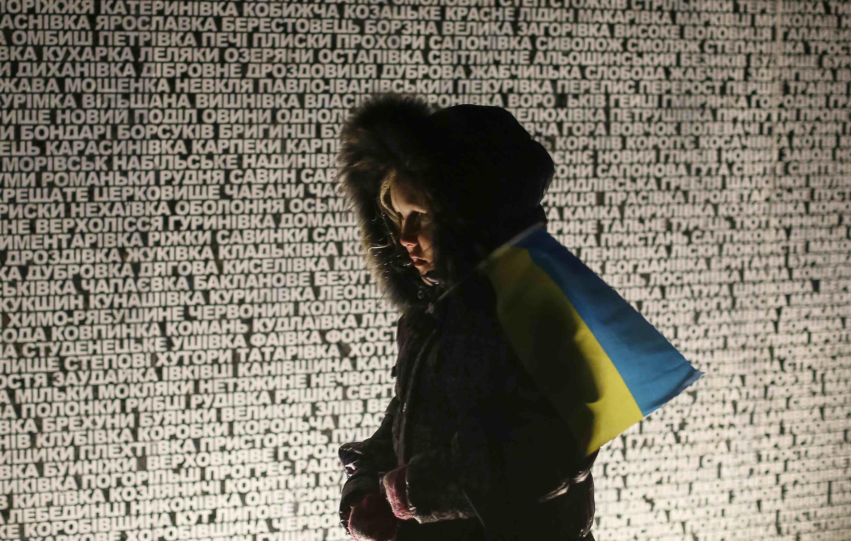 Một phụ nữ đi qua trước công trình tưởng niệm các nạn nhân của nạn đói 1932-1933 ở Ukraina.