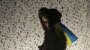 Une femme passe devant un monument commémorant les grandes famines des années 1932-33 en Ukraine.