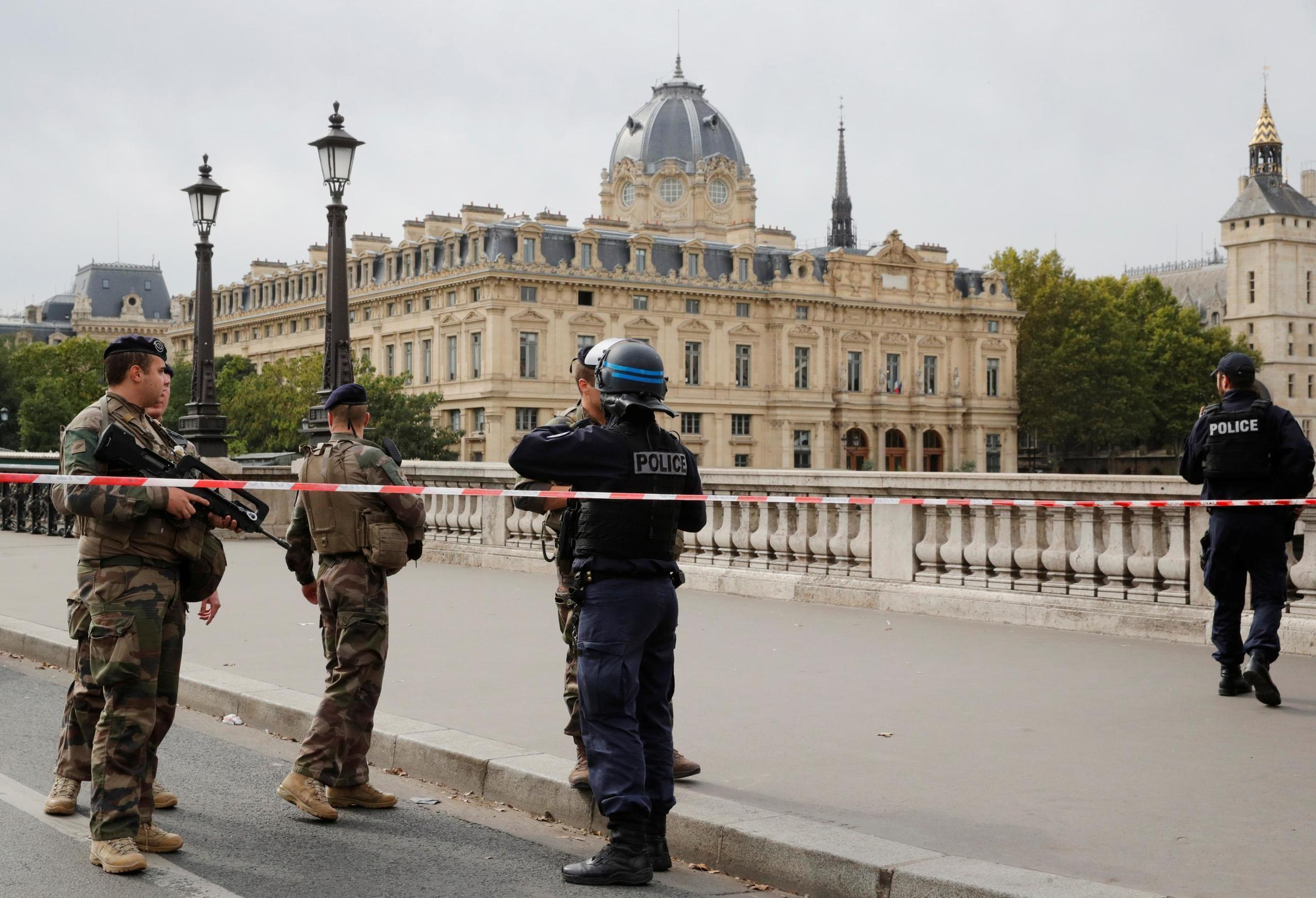 French police and soldiers stand guard at a security cordon around the Paris police headquarters following an attack that killed four staff members, 3 October 2019.
