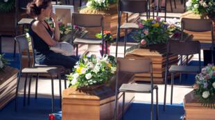 Una mujer junto a los ataúdes de las víctimas del terremoto que azotó el centro de Italia.