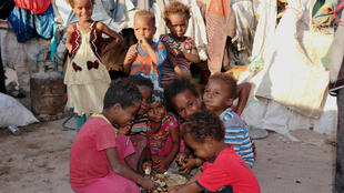 Crianças a comer pão num campo de refugiados no Iémen.