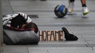 Một người vô gia cư phải ngủ ngoài đường tại trung tâm thành phố Milano, bên cạnh là tấm biển ghi « Tôi đói ». Ảnh chụp ngày 17/06/2016.