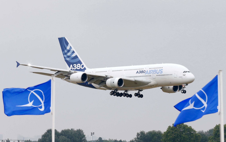 Un Airbus A380, le plus grand avion de ligne du monde, survole les drapeaux de Boeing au 51e Salon du Bourget, le 15 juin 2015.