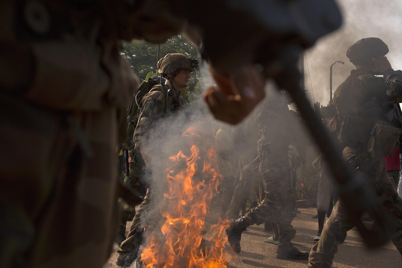 Des soldats français de l'opération Sangaris tentent de disperser une foule à proximité d'une barricade, dans une rue de Bangui, le 22 janvier.