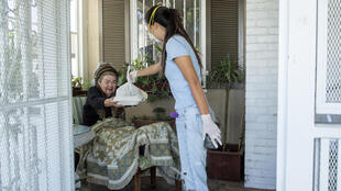 "Mira Kwon, the 16 year-old high school student who launched the Los Angeles branch of ""Zoomers to Boomers"", delivers groceries to Mary Navarro, an elderly disabled woman -- the service is now available in more than a dozen US cities"