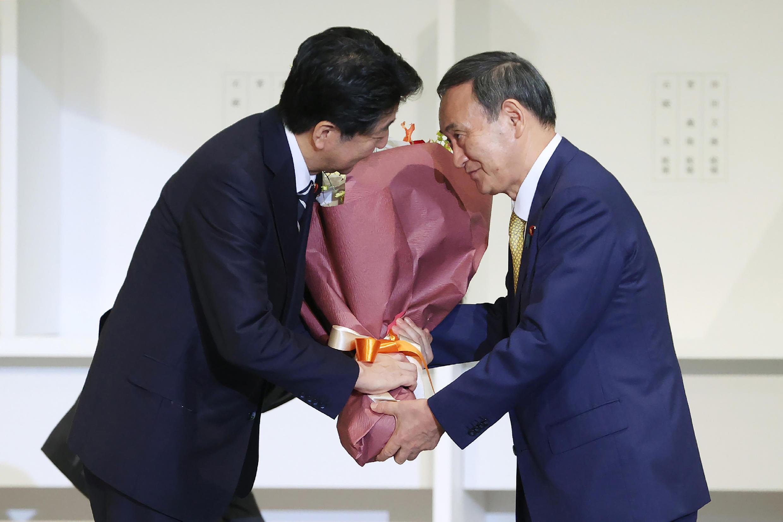 El recién elegido líder del Partido Liberal Democrático de Japón, Yoshihide Suga (dcha), entrega flores al primer ministro saliente Shinzo Abe tras la elección del partido gobernante en Tokio el 14 de septiembre de 2020