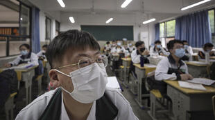 Students wearing protective face masks to help curb the spread of the new coronavirus attend a class at a high school in Wuhan in central China's Hubei province, Wednesday, May 6, 2020. Senior students returned to classes on Wednesday in the central Chinese city of Wuhan, the epicenter of the coronavirus pandemic, after no new cases or deaths were reported from the outbreak that had prompted a 76-day quarantine in the city of 11 million. (Chinatopix via AP)