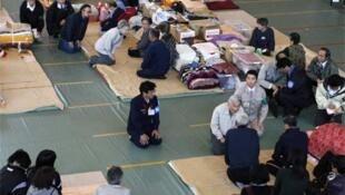 Japanese Empress Michiko (top) visits a shelter at Minamisanriku, Miyagi Prefecture, Wednesday