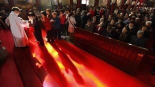 Católicos chineses fazem fila para comungar na Catedral Xishiku, controlada pelo Estado na zona norte de Pequim.