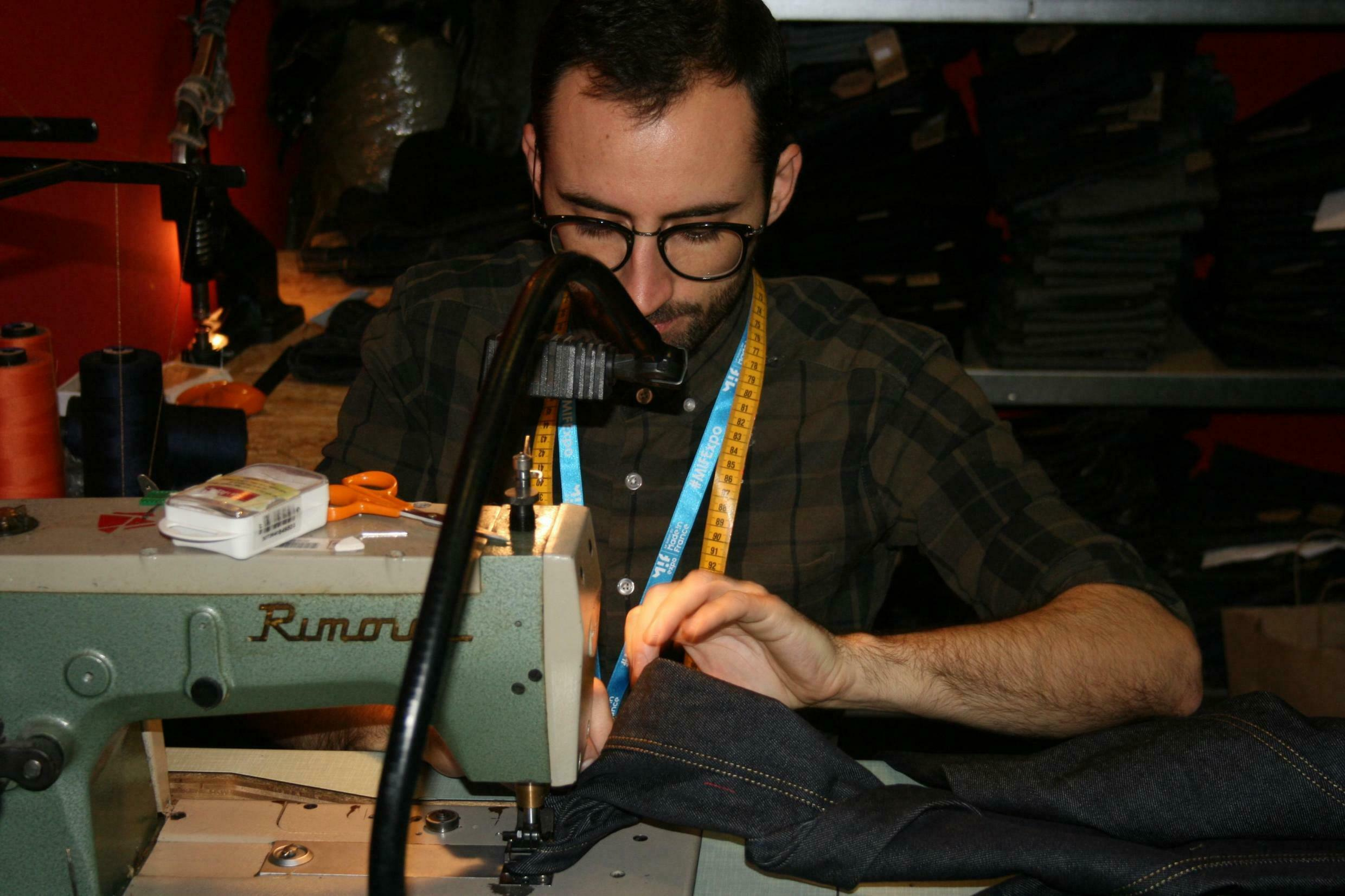 """A dressmaker from the Davy Dao jean factory in Nancy produces a bespoke jean for a customer at the """"Made in France"""" fair at Porte de Versailles in Paris, 10 November 2019"""