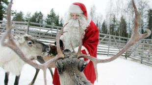 (Photo d'illustration) Un homme déguisé en père Noël donne à manger à un renne dans une ferme de Rovaniemi, au nord de la Finlande, le 19 décembre 2007.