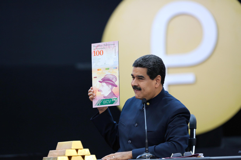 Le président vénézuélien Nicolas Maduro montre l'agrandissement d'un nouveau billet de 100 bolivars à Caracas, le 22 mars 2018.