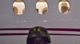 Yahya Hammeh regarde à travers le hublot de l'avion du président guinéen, Alpha Condé.
