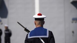 Un soldat de la marine française se tient devant la visite du ministre français de la Défense à bord du FREMM.