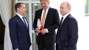 Le président russe Vladimir Poutine (d),, le prote-parole du Kremlin Dmitri Peskov (c), le premier ministre russe Dmitri Medvedev (g), avant une rencontre avec la chancelière allemande Angela Merkel, à Sotchi, le 18 mai 2018.