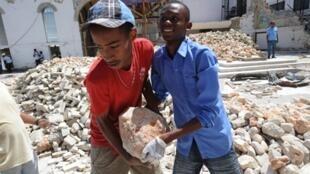 Six mois après le tremblement de terre, les travaux de reconstruction se poursuivent à Haïti. Ici, des étudiants qui déblayent les décombres d'une église.