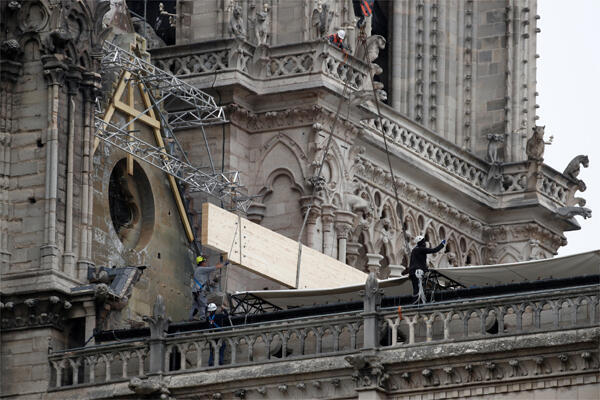 Des ouvriers installent des bâches provisoires pour protéger la cathédrale Notre-Dame de la pluie.