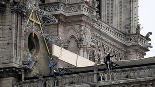 Workers install tarps to protect the fire-damaged Notre-Dame Cathedral in Paris from rain, 24 April 2019.