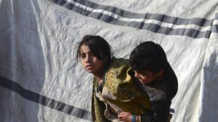 Niños juegan junto a una tienda de campaña en un campamento para familias de desplazados en el distrito de Dand, de la provincia de Kandahar, Afganistán, el 7 de enero de 2021.
