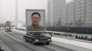 A limousine carrying a portrait of late North Korean leader Kim Jong-il leads his funeral procession