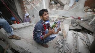 Un proche d'une des personnes disparues à la suite de l'effondrement de l'immeuble à proximité de Dacca, au Bangladesh.