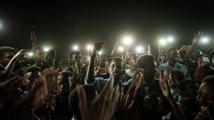 People chant slogans as a young man recites a poem illuminated by mobile phones, in Khartoum, June 19, 2019