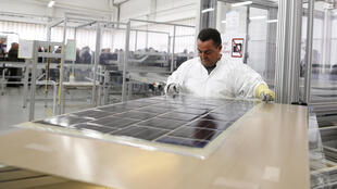 A man works on photovoltaic panels during the launch of the work for the construction of the first solar road at a factory in Tourouvre.