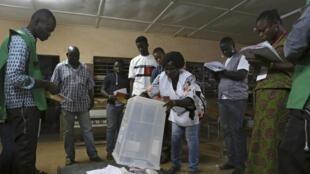 Décompte des bulletins de vote sous l'oeil attentif des observateurs de ces élections présidentielle et législatives, dans un bureau de Ouagadougou, le 29 novembre 2015.