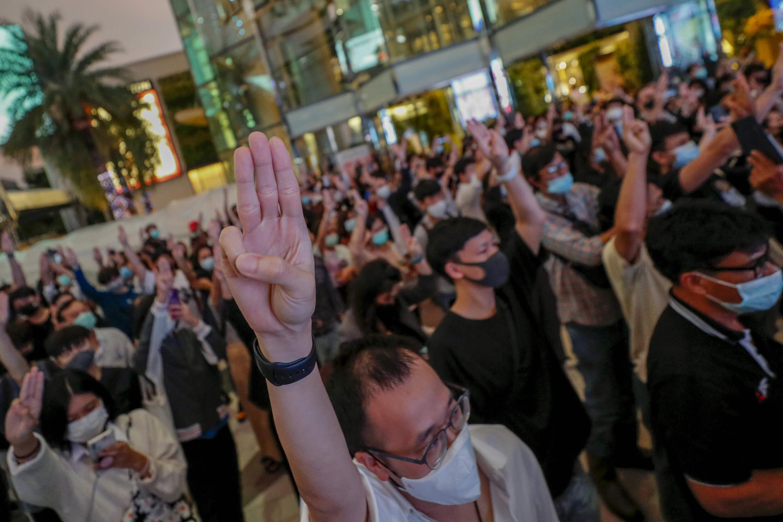 Les militants pro-démocratie saluent à trois doigts tout en écoutant l'hymne national devant Siam Paragon, l'un des plus grands centres commerciaux, à Bangkok, en Thaïlande, le mardi 20 octobre 2020.