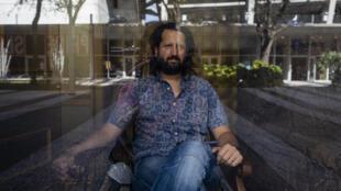 """Michel Hausmann, de 39 años, es el director artístico del Miami New Drama, la compañía residente del histórico Teatro Colony. Aquí posa tras la vitrina de una tienda comercial en Lincoln Road, escenario de uno de los actos de """"Siete pecados capitales""""."""